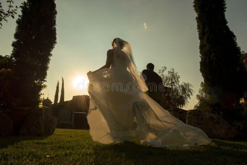 _bride and新娘和新郎跑在日落,庭院婚礼在日落 免版税库存图片