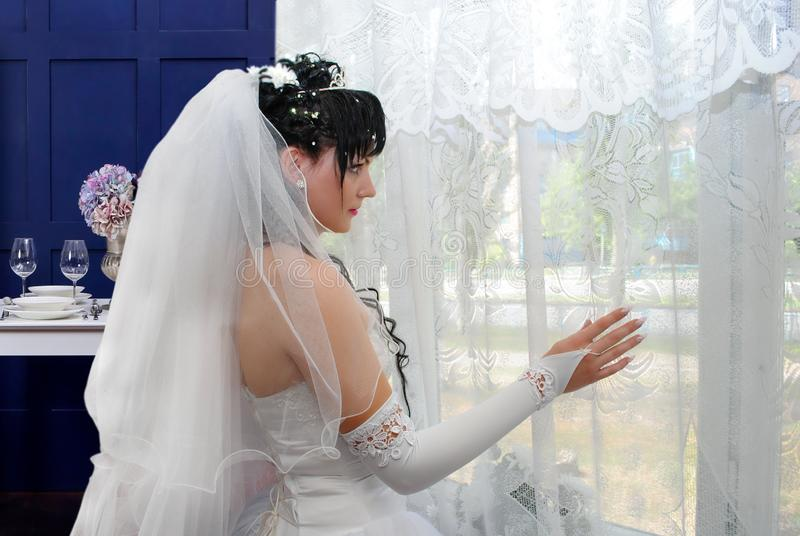 Bride in anticipation of a loved one before the wedding. Bride in front of the window in anticipation of a loved one before the wedding royalty free stock photos