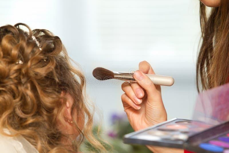 Bride applying wedding make-up royalty free stock photography