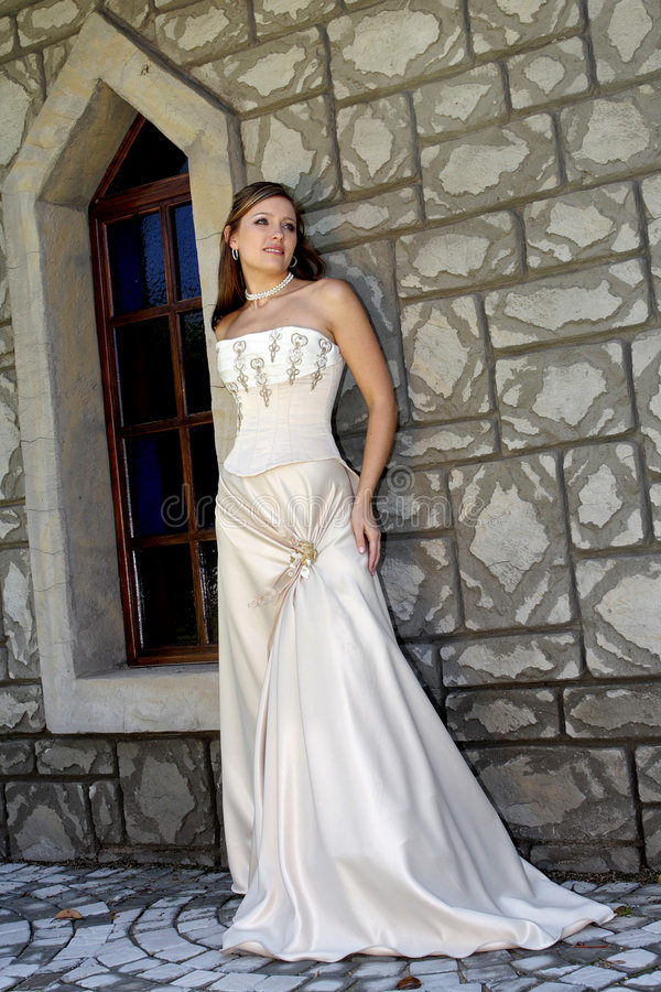 Bride Arch. A bride standing against a wall in her dress stock image