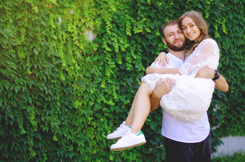 Bride in the arms of the groom`s white dress stock photo