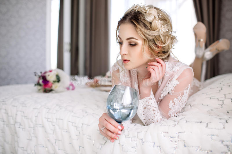 The bride in a Bathrobe to the bedroom window in the morning stock image