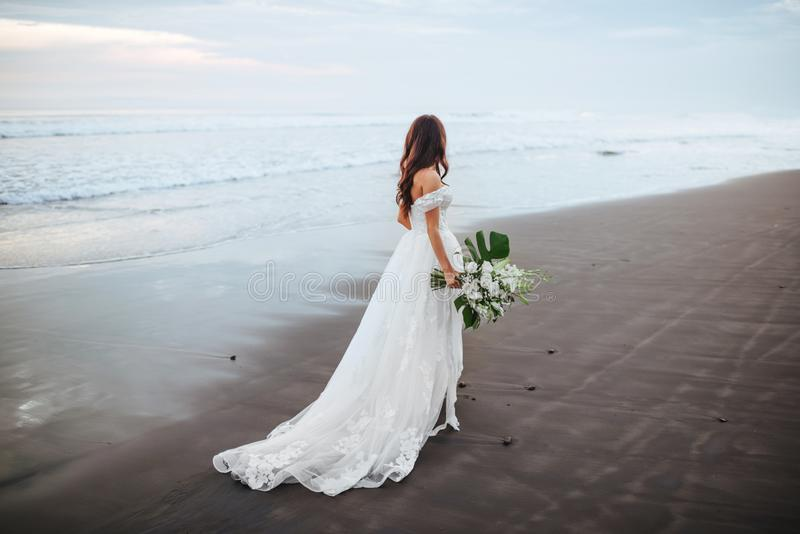 Bride on a beach in the blue water. With a bouquet in hands on sunset stock photo