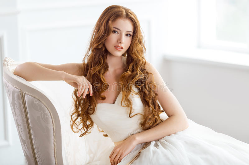 Bride in beautiful dress sitting resting on sofa indoors. Bride in beautiful dress sitting on sofa indoors in white studio interior like at home. Trendy wedding stock images