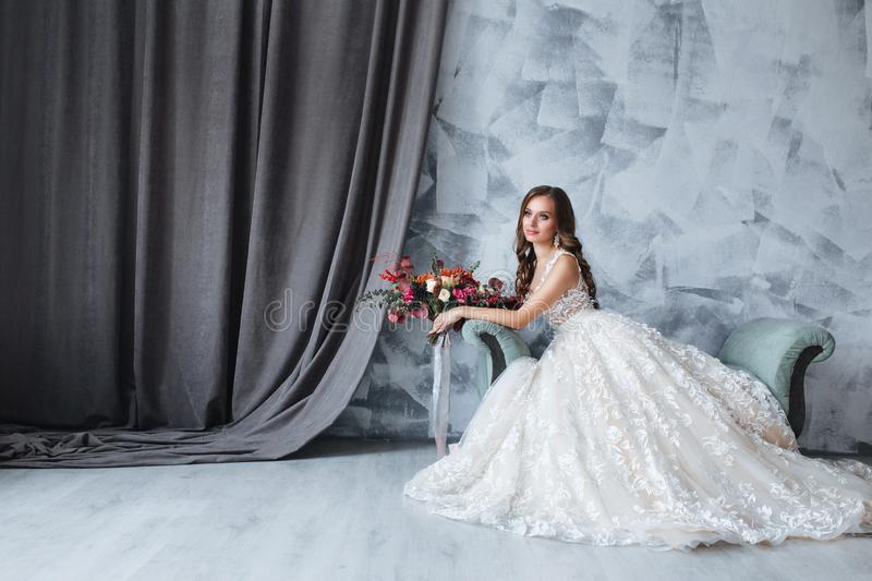 Bride in beautiful dress sitting on sofa indoors in white studio interior like at home. Bride in beautiful dress with wedding bouquet sitting on sofa indoors in royalty free stock photos