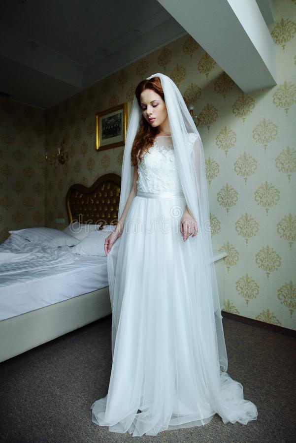 Beautiful redhair lady in elegant white wedding dress. Fashion portrait of model indoors. Beauty woman standing. stock photo