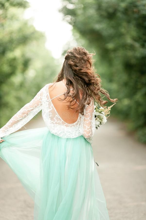 Bride goes on forest road with bouquet in hands, back view. stock photos