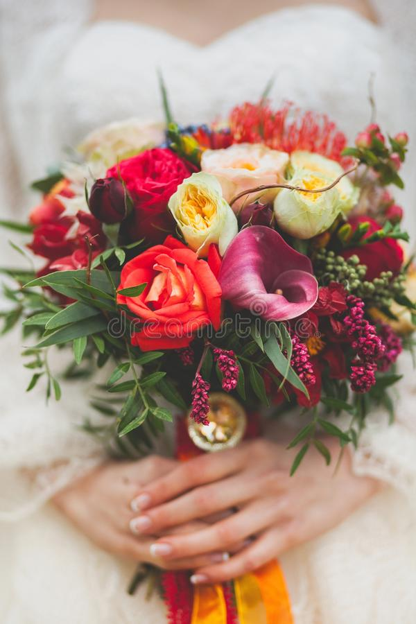 The bride in a beautiful white wedding dress holds a beautiful autumn wedding bouquet. Beautifully decorated multi-colored bouquet. Of flowers of several kinds royalty free stock images