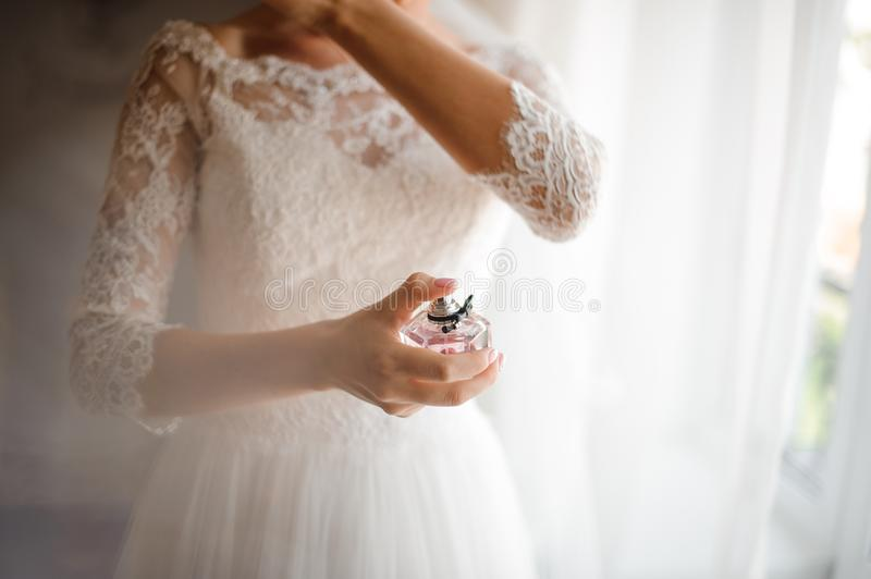 Bride in a beautiful white wedding dress with a perfume stock images