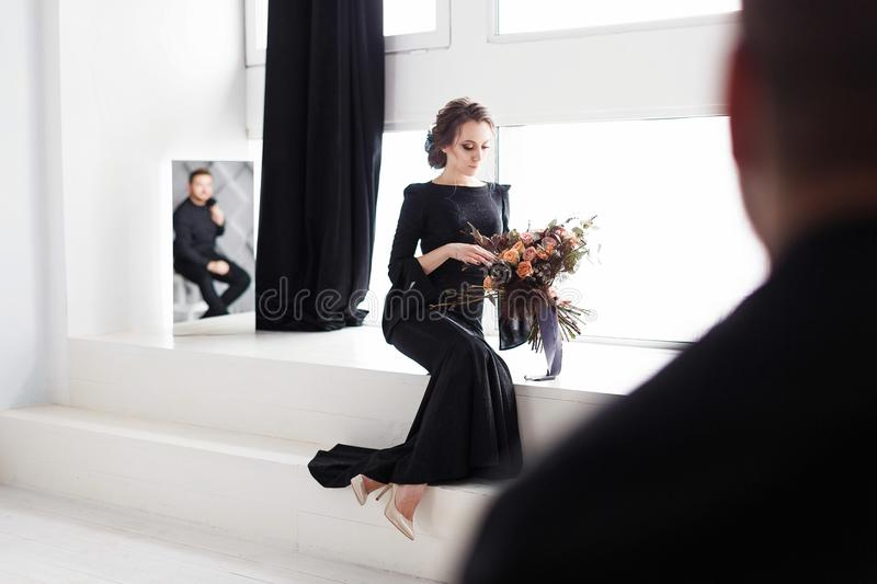 The bride in black dress. Reflecting in the mirror. White studio room with windows. Horizontal shot with blurred groom royalty free stock images