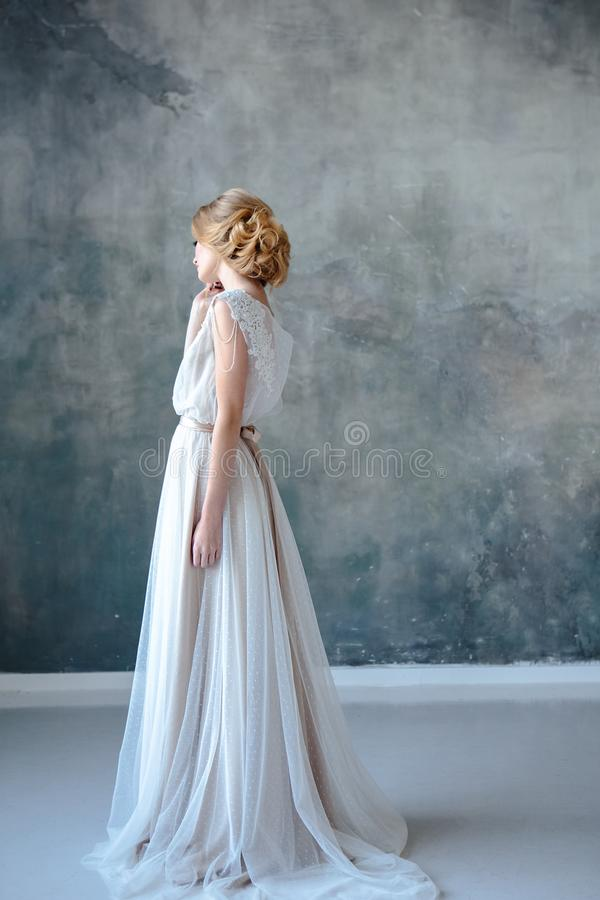 Bride blonde woman in a modern color wedding dress with elegant hair style and make up. Fashion beauty portrait stock photos