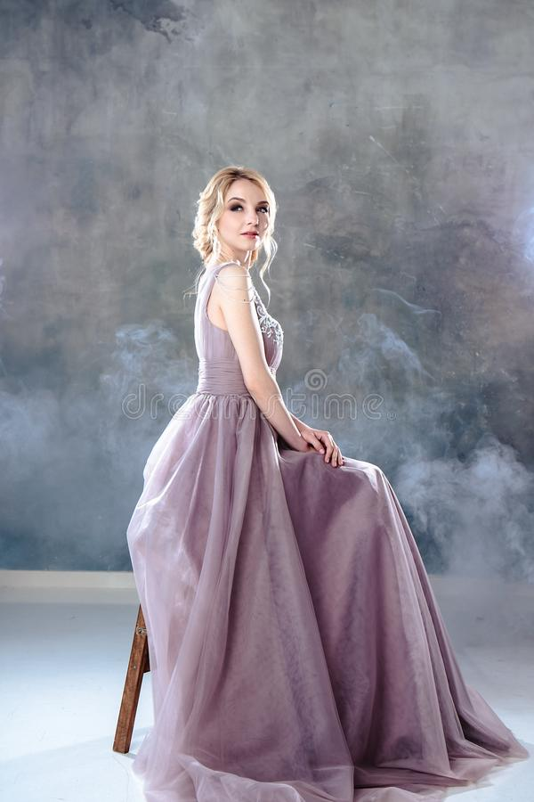 Bride blonde woman in a modern color wedding dress with elegant hair style and make up. Fashion beauty portrait stock images