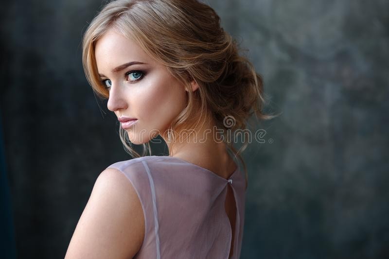 Bride blonde woman in a modern color wedding dress with elegant hair style and make up. Fashion beauty portrait. Over textured background royalty free stock photo