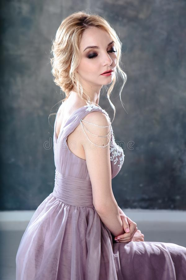 Bride blonde woman in a modern color wedding dress with elegant hair style and make up. Fashion beauty portrait stock photo