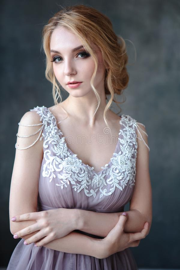 Bride blonde woman in a modern color wedding dress with elegant hair style and make up. Fashion beauty portrait royalty free stock photos