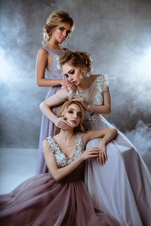 Bride blonde young women in a modern color wedding dress with elegant hair style and make up. Fashion beauty portrait composition. Over textured background royalty free stock photo