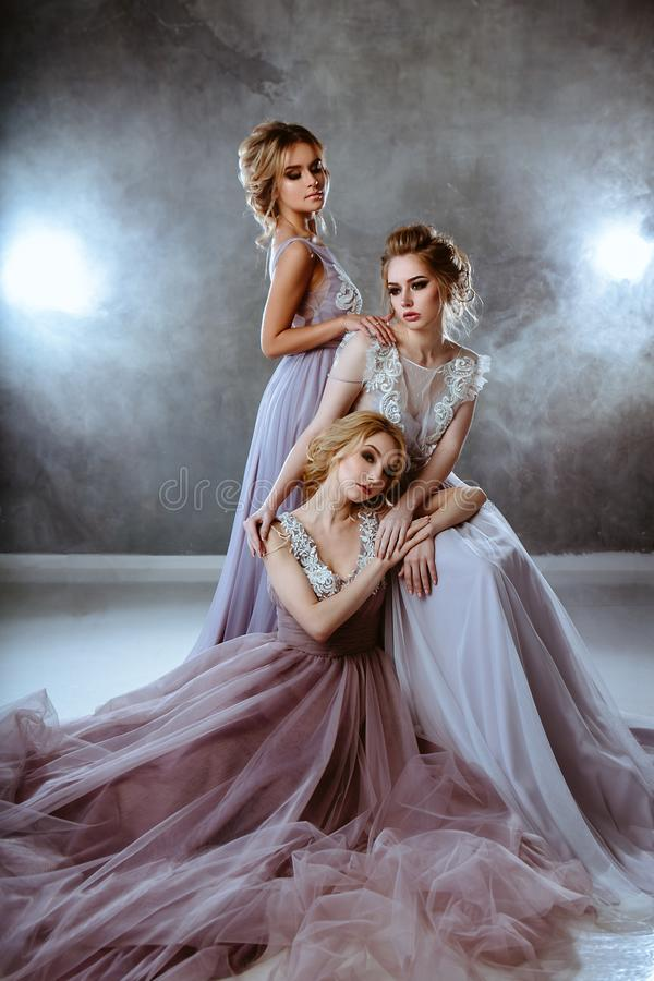 Bride blonde young women in a modern color wedding dress with elegant hair style and make up. Fashion beauty portrait composition stock photos