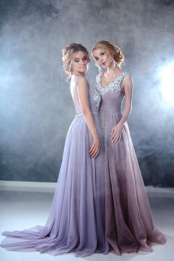 Bride blonde young women in a modern color wedding dress with elegant hair style and make up. Fashion beauty portrait composition royalty free stock photo