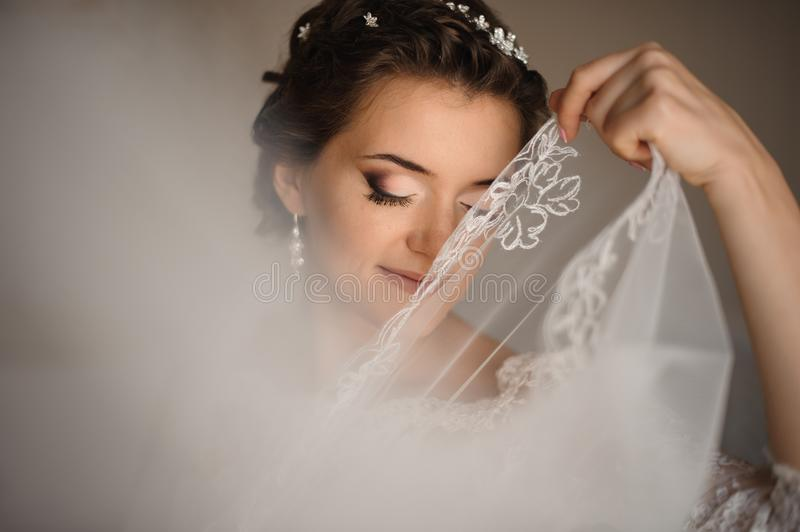 Bride with blue eyes covers her lips with a veil stock images