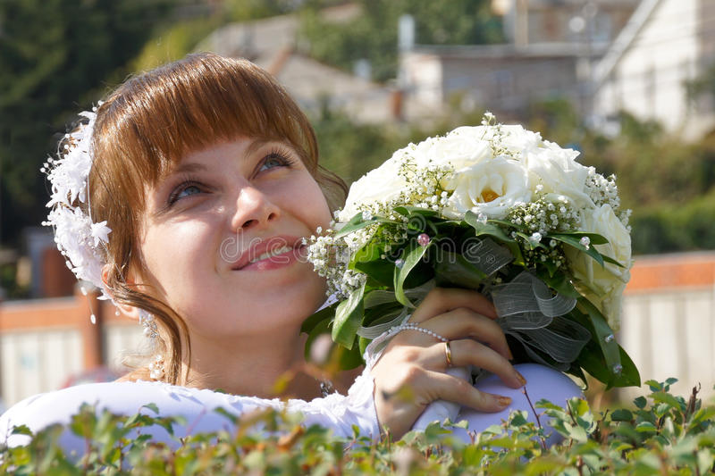 Bride with bouquet. The bride with a bouquet in a wedding walk stock photo