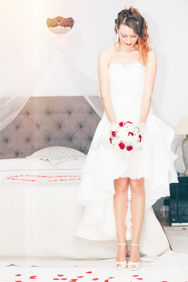 Bride with bouquet. Bedroom marriage bed. stock photography