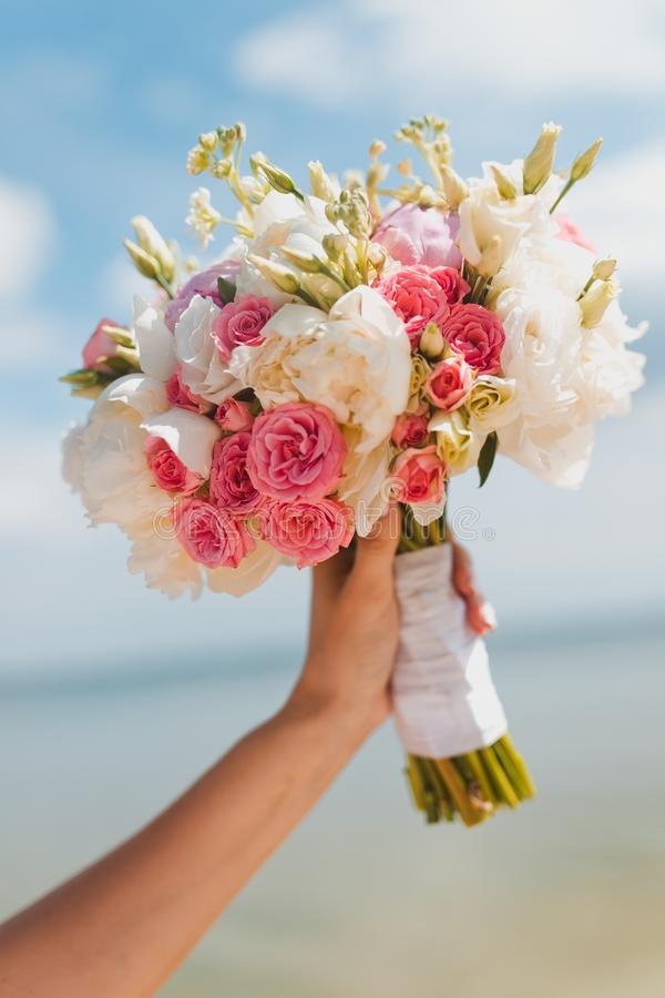 Bride bouquet on blue sky. Bride bouquet in hamd on blue sky royalty free stock images