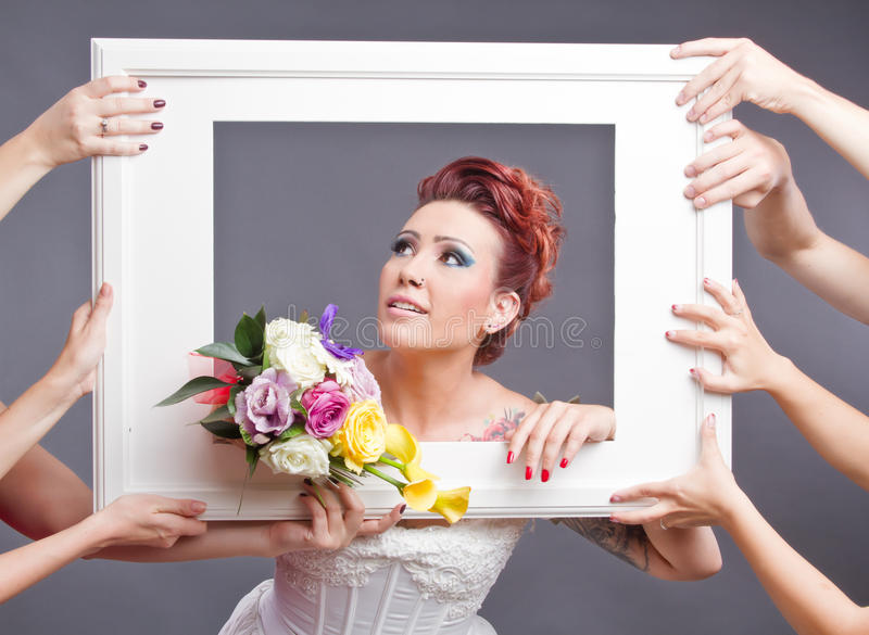 Bride with bouquet in frame. Beautiful happy bride in white wedding dress holding bouquet of flowers in a white frame held up by guests' hands stock image