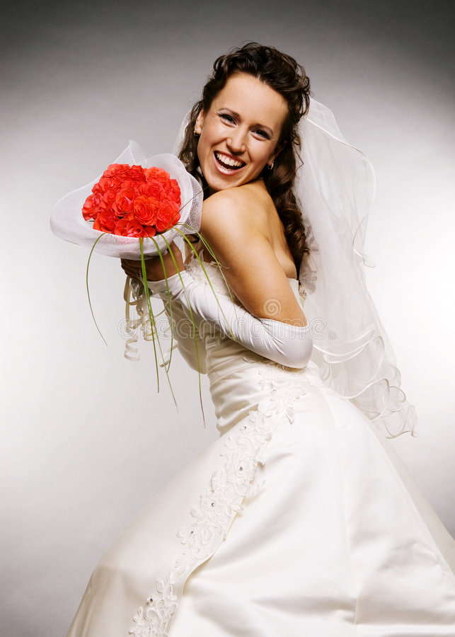 Bride with bouquet of roses. Laughing bride with bouquet of roses stock photo