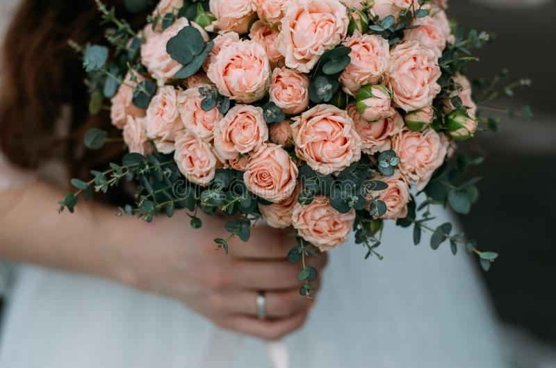 Bride with bouquet of roses in hands stock photography