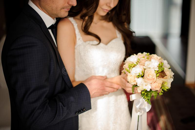 Bride and bridegroom looking together at the bouquet of roses stock images