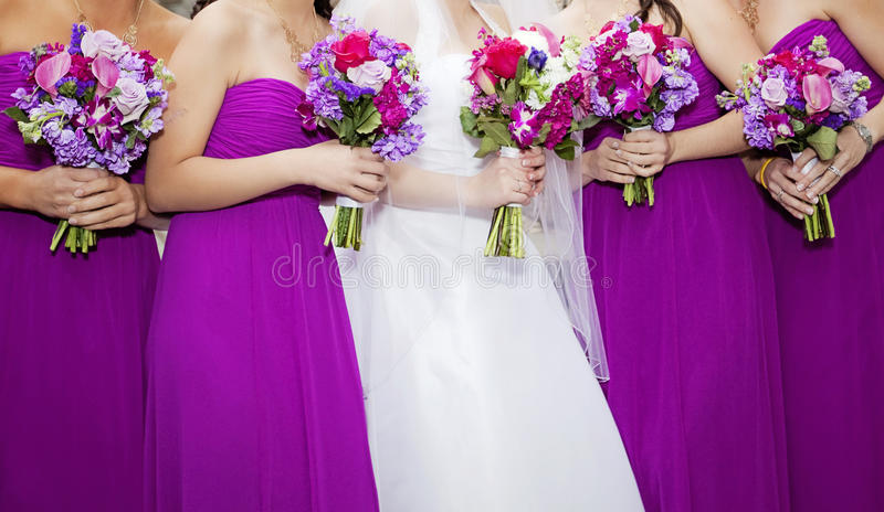 Bride and Bridemaids. Bride and four bridesmaids wearing purple holding bouquets