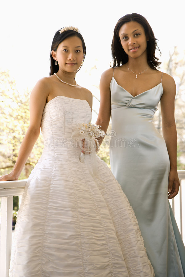 Bride and bridesmaid. A portrait of a African-American maid of honor and Asian bride leaning against railing royalty free stock photos