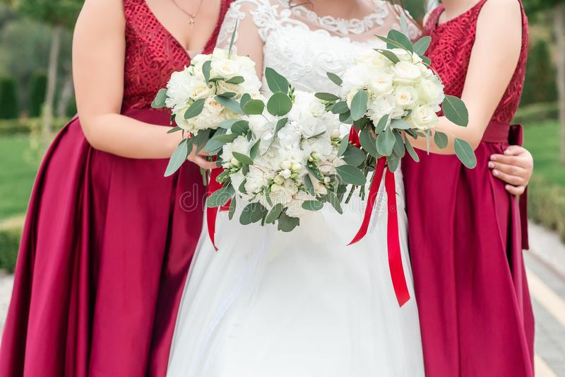 Bride and bridesmaid are holding bouquets of flowers in hands. Bridesmaid are on background. Bride is holding a wedding bouquet. stock images