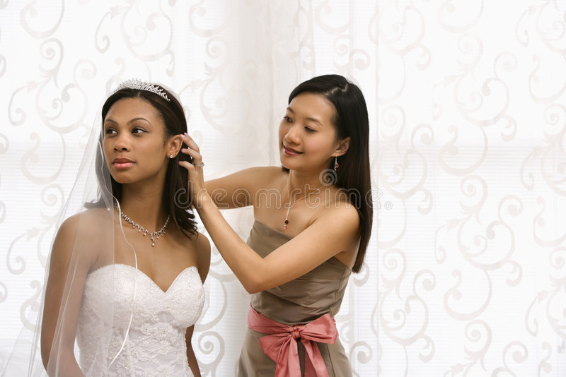 Bride and bridesmaid portrait. Asian bridesmaid fixing African-American bride's hair stock images