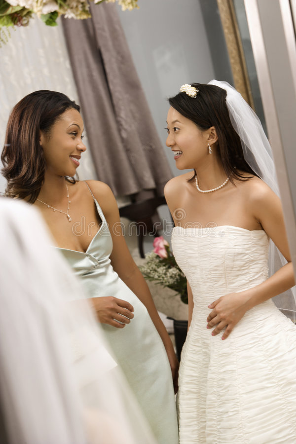 Bride and bridesmaid talking. Asian bride and African-American bridesmaid talking to each other royalty free stock image