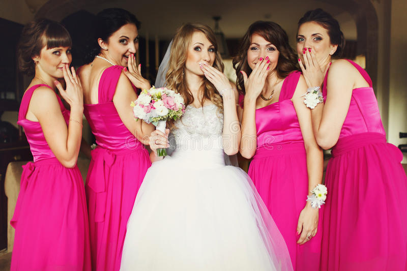 Bride and bridesmaids flirt standing in the restaurant.  royalty free stock photography