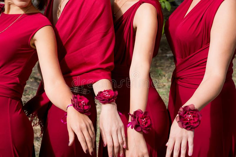 Bride and bridesmaids with red bracelets on hands. Close up hands. royalty free stock image