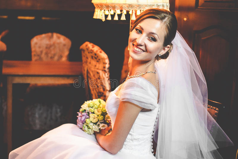 Bride with a broad smile sits in a wooden cabinet stock photography