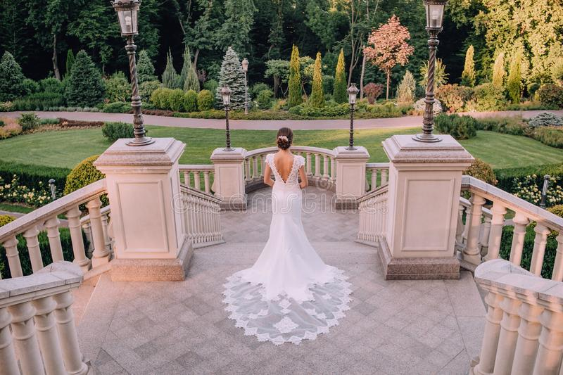 Bride chic dress architecture lanterns beautiful garden. Bride in a chic dress on a background of architecture with lanterns and a beautiful garden stock image
