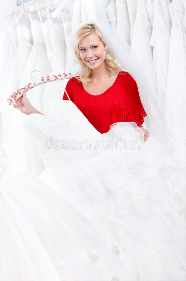 Bride is choosing the dress to try on stock photography