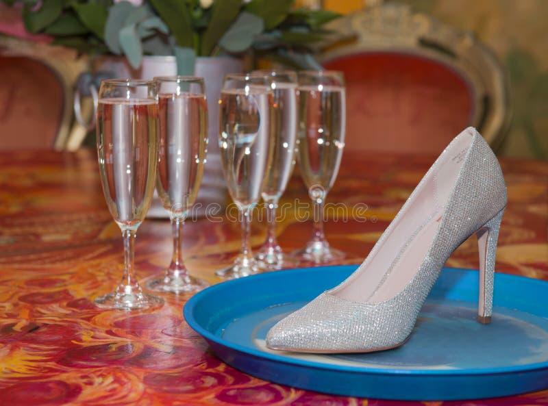 Bride com flores sobre a mesa Calçado de casamento rosa na mesa vermelha com óculos de champanhe fotos de stock