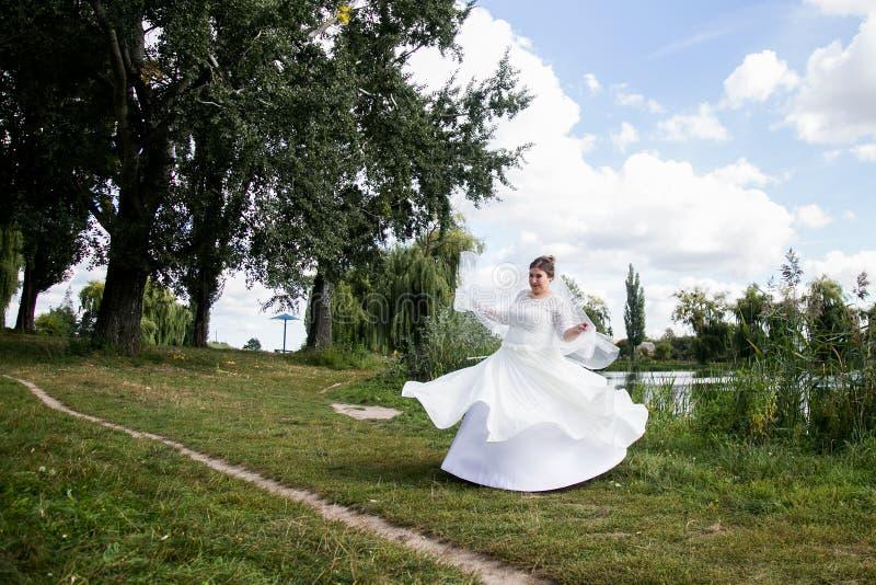 Bride dancing in park royalty free stock photo