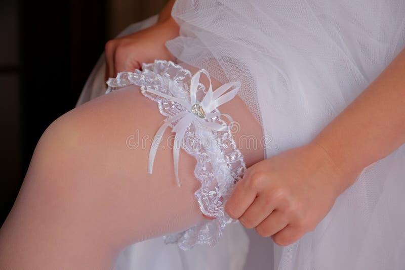 Bride dress on a leg garter before wedding. Young bride dress on a leg garter before wedding ceremony. Closeup view stock photo
