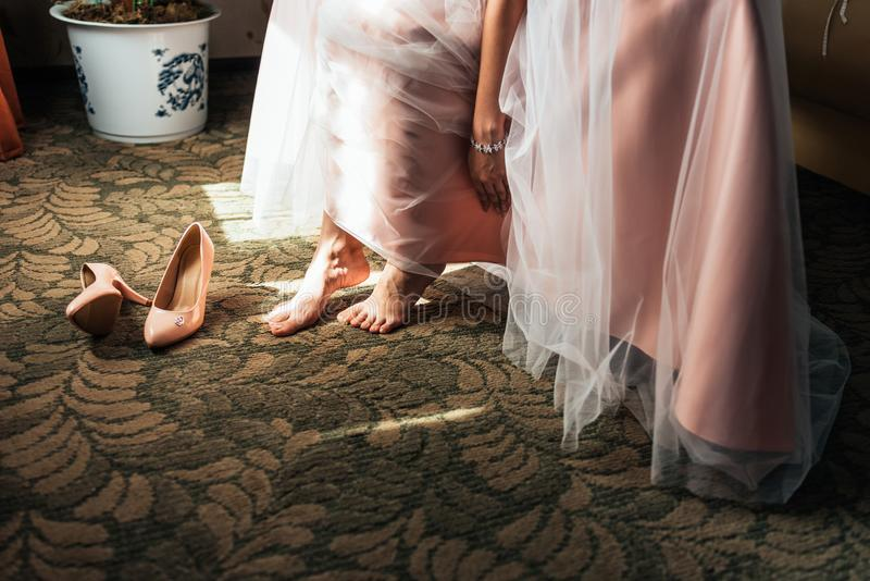 Bride dresses shoes before the wedding ceremony. Charges of the bride. Closeup detail of bride putting on high heeled sandal. Wedding shoes. Wedding bride shoes royalty free stock photo