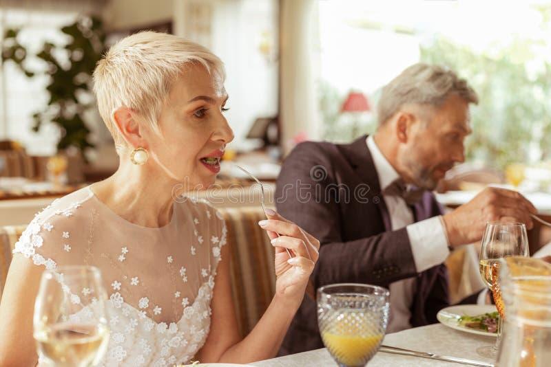 Beautiful aged bride eating salad while celebrating wedding royalty free stock photo