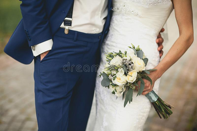 The bride in an elegant wedding dress is holding a beautiful bouquet of white roses, buds, green leaves and decorative items. Embrace the newlyweds, the hands stock photos