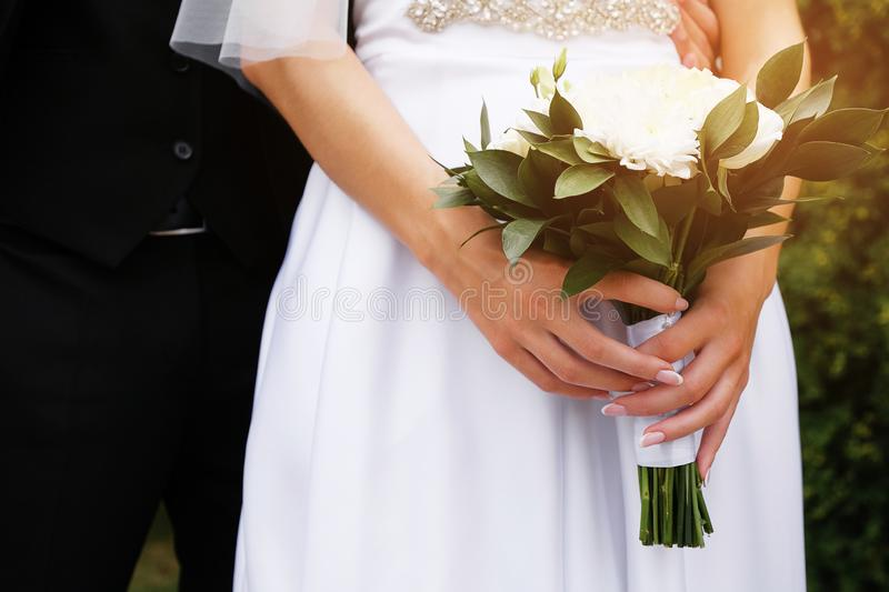 The bride in an elegant wedding dress is holding a beautiful bouquet of white roses and chrysanthemums and green leaves. Embrace royalty free stock image