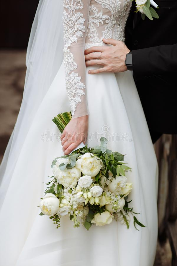 The bride in an elegant wedding dress holds a beautiful bouquet of different flowers and green leaves. Wedding theme royalty free stock photos