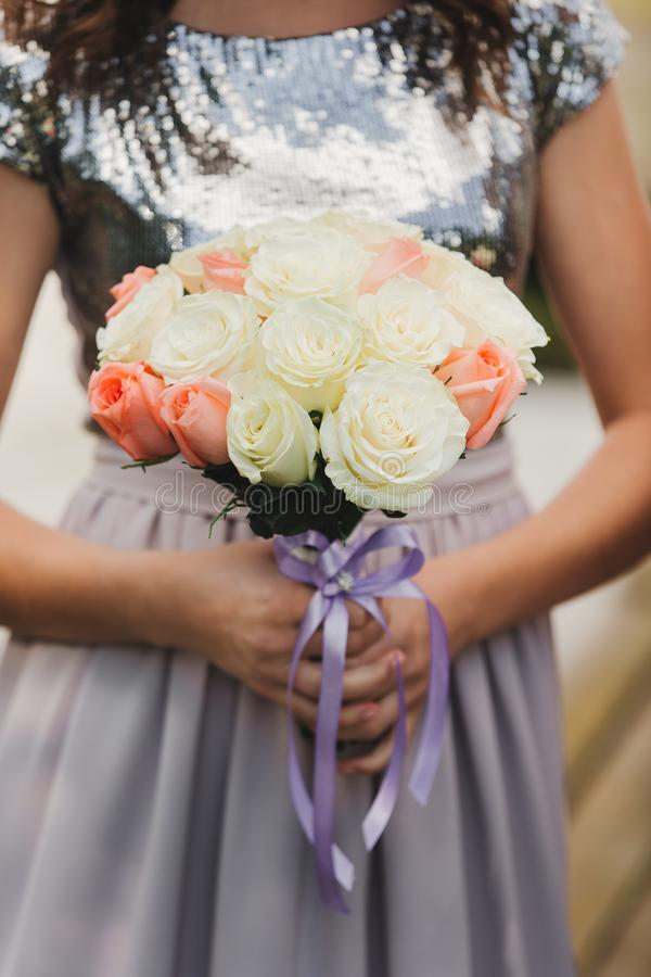 The bride in an elegant wedding dress holds a beautiful bouquet of different flowers and green leaves. Wedding theme stock photography