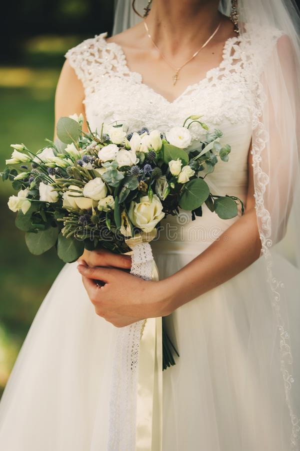 The bride in an elegant wedding dress holds a beautiful bouquet of different flowers and green leaves. Wedding theme stock image